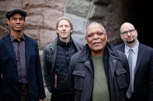 The Billy Hart Quartet standing near an underpass.